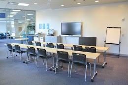 兩排書桌,每排有2把椅子,面向中央大屏幕平板顯示器