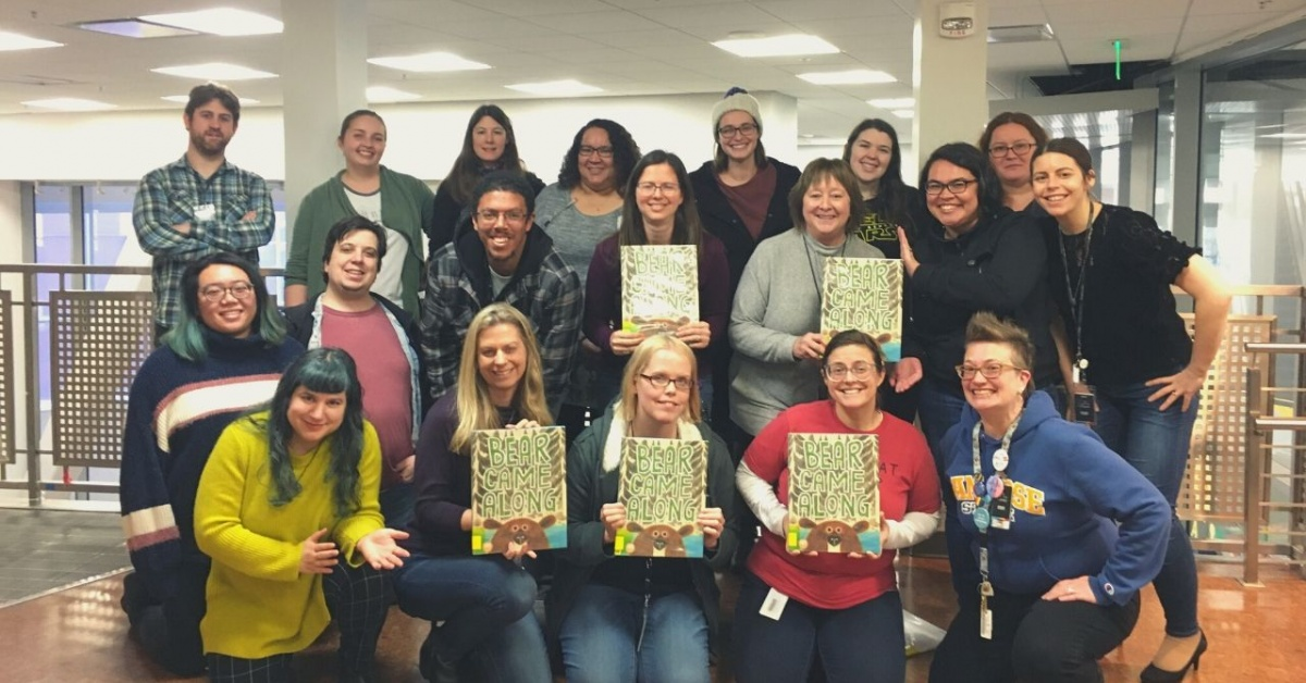 "Group shot of 19 library staff members holding copies of their Mock Caldecott selection ""Bear Came Along"""
