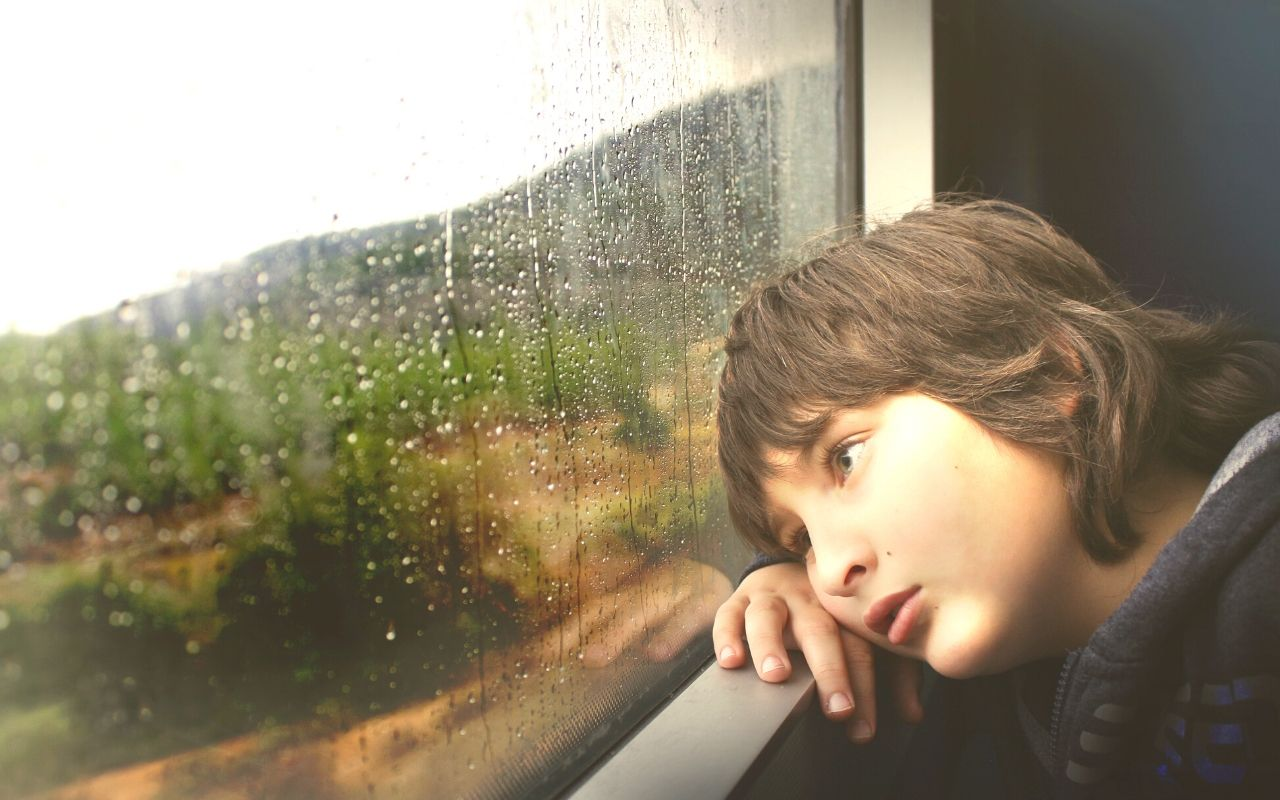 Bored child staring out at a rainy window.