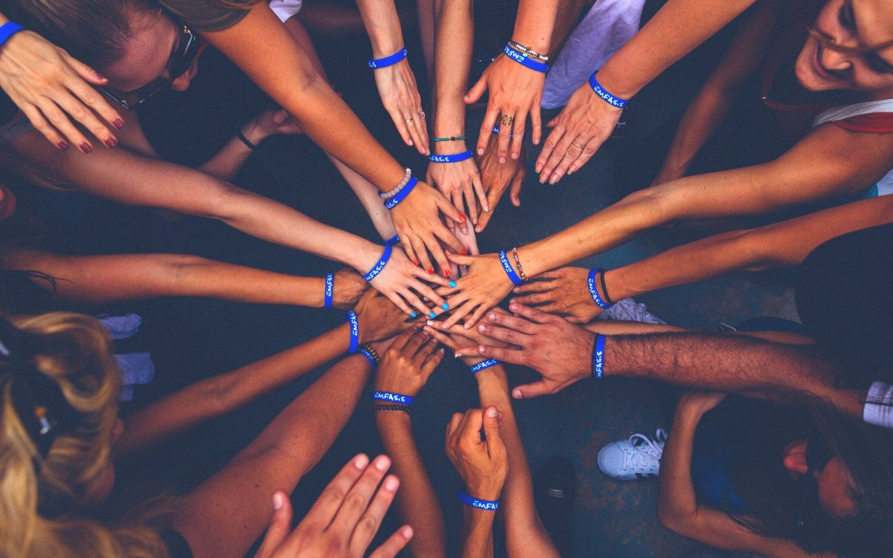 A group of hands touching in the center.