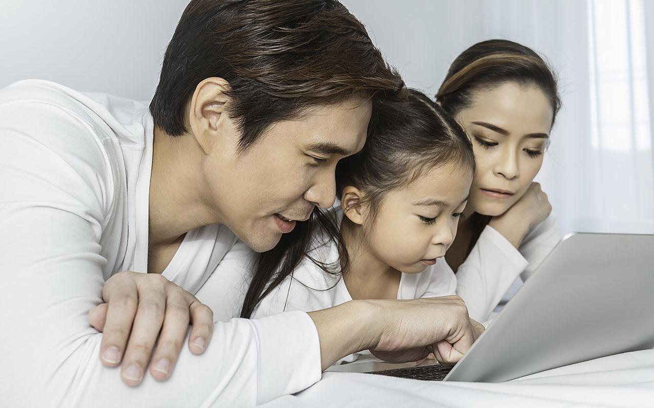 父母在筆記本電腦上幫助他們的小女兒。