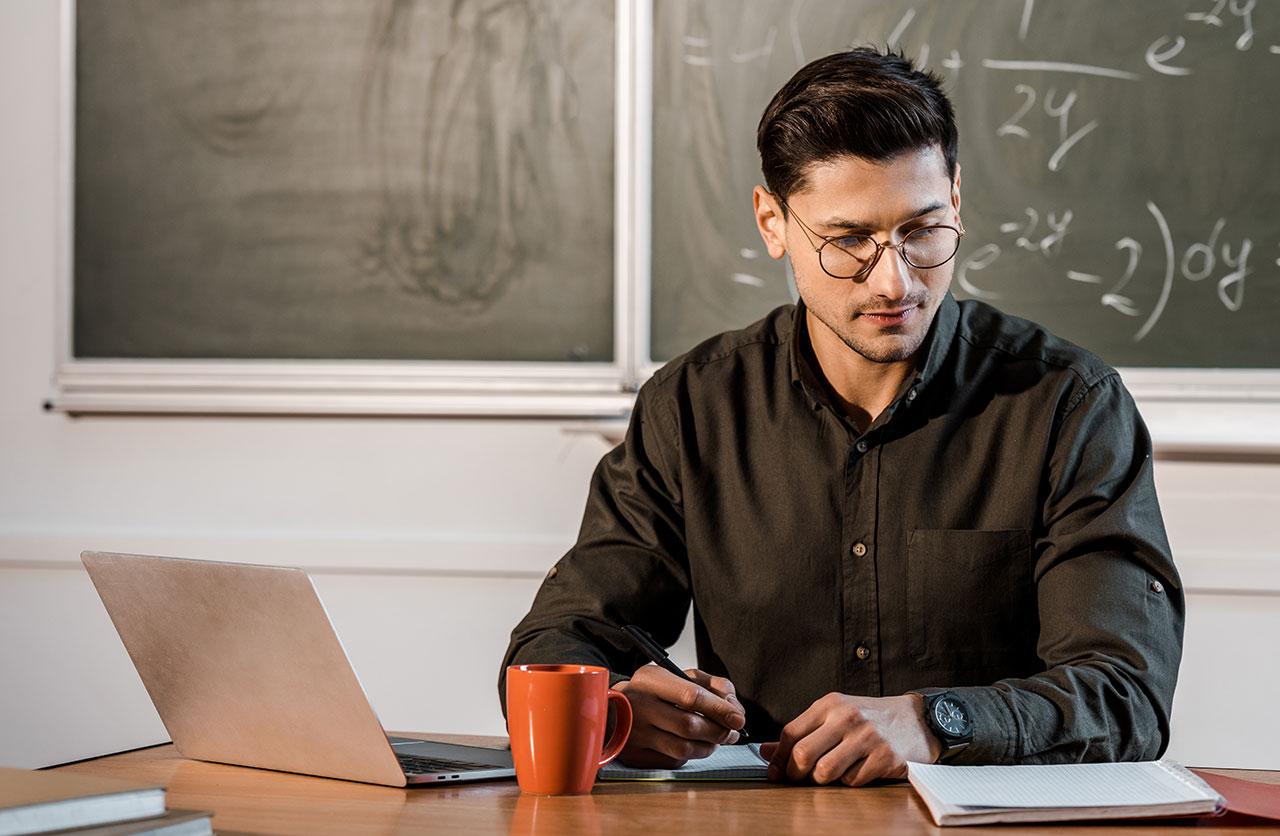 書桌的數學老師有膝上型計算機的學習他的筆記。