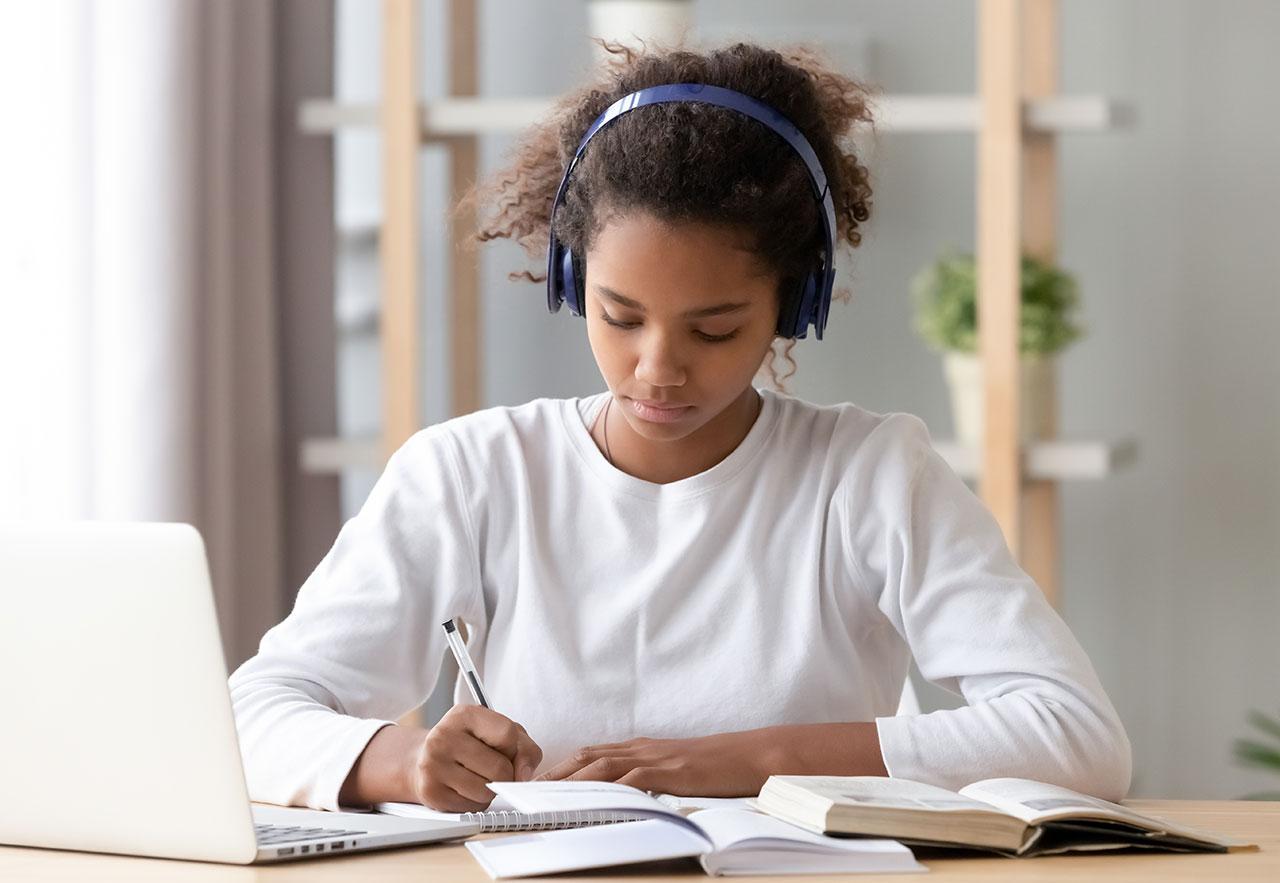 青少年的女孩在做筆記時聽著耳機聽著她的筆記本電腦上的一堂課。