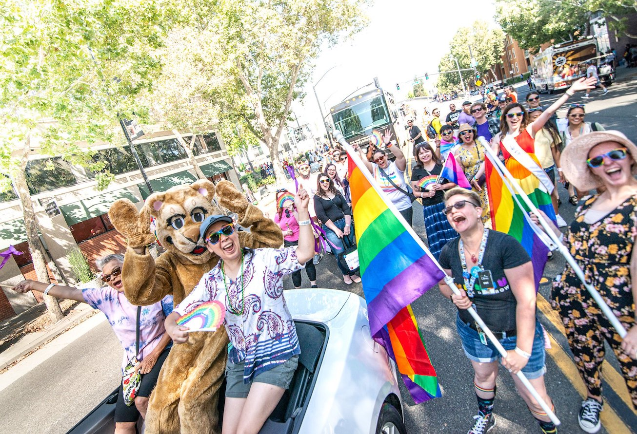 A large group of happy smiling people, including one dressed in a cougar animal suit, waving rainbow flags at a LGBTQIA+ Pride Parade.