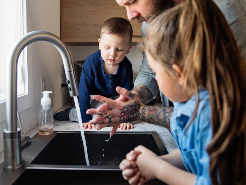Padre mostrando a los niños cómo lavarse las manos en el fregadero.