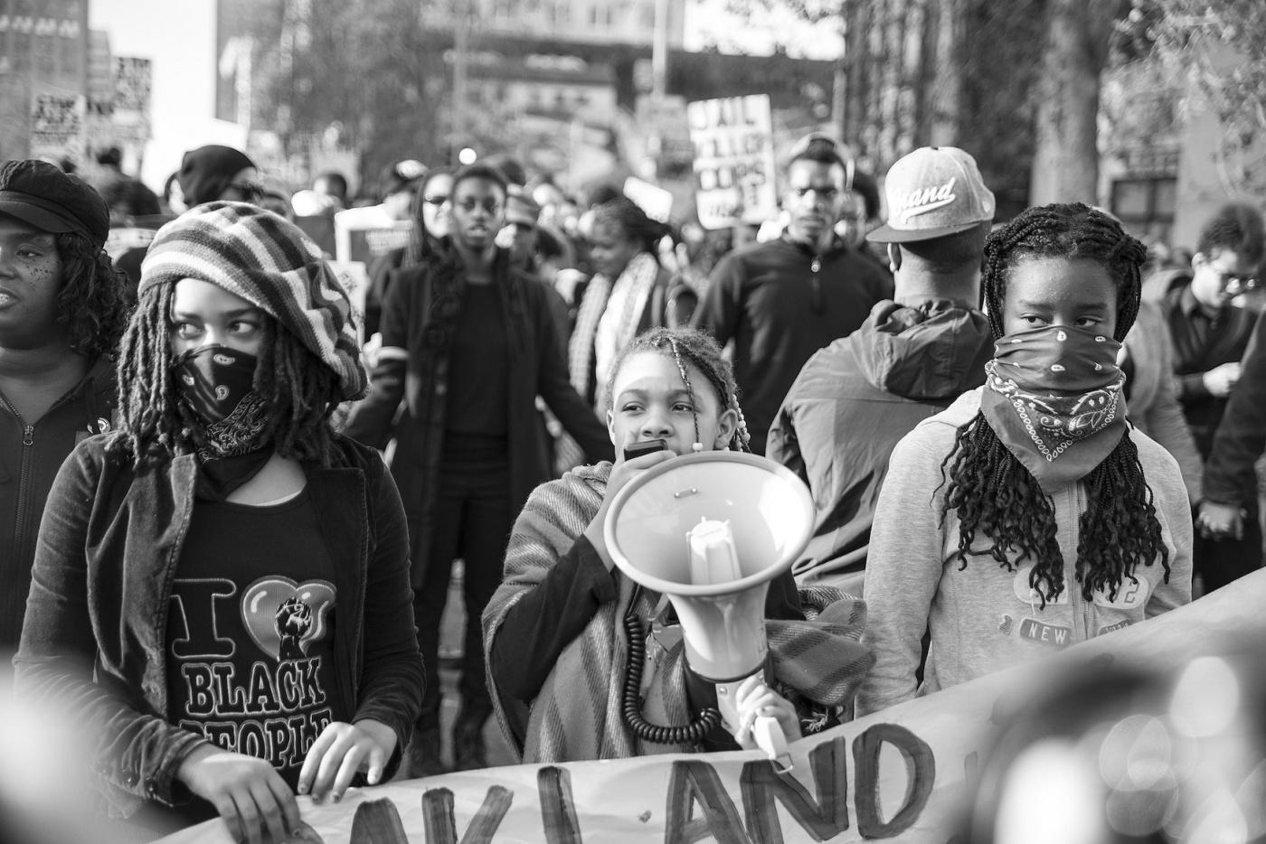 """一群""""黑色生活""""抗議者在遊行,遊行者與擴音器交談。"""