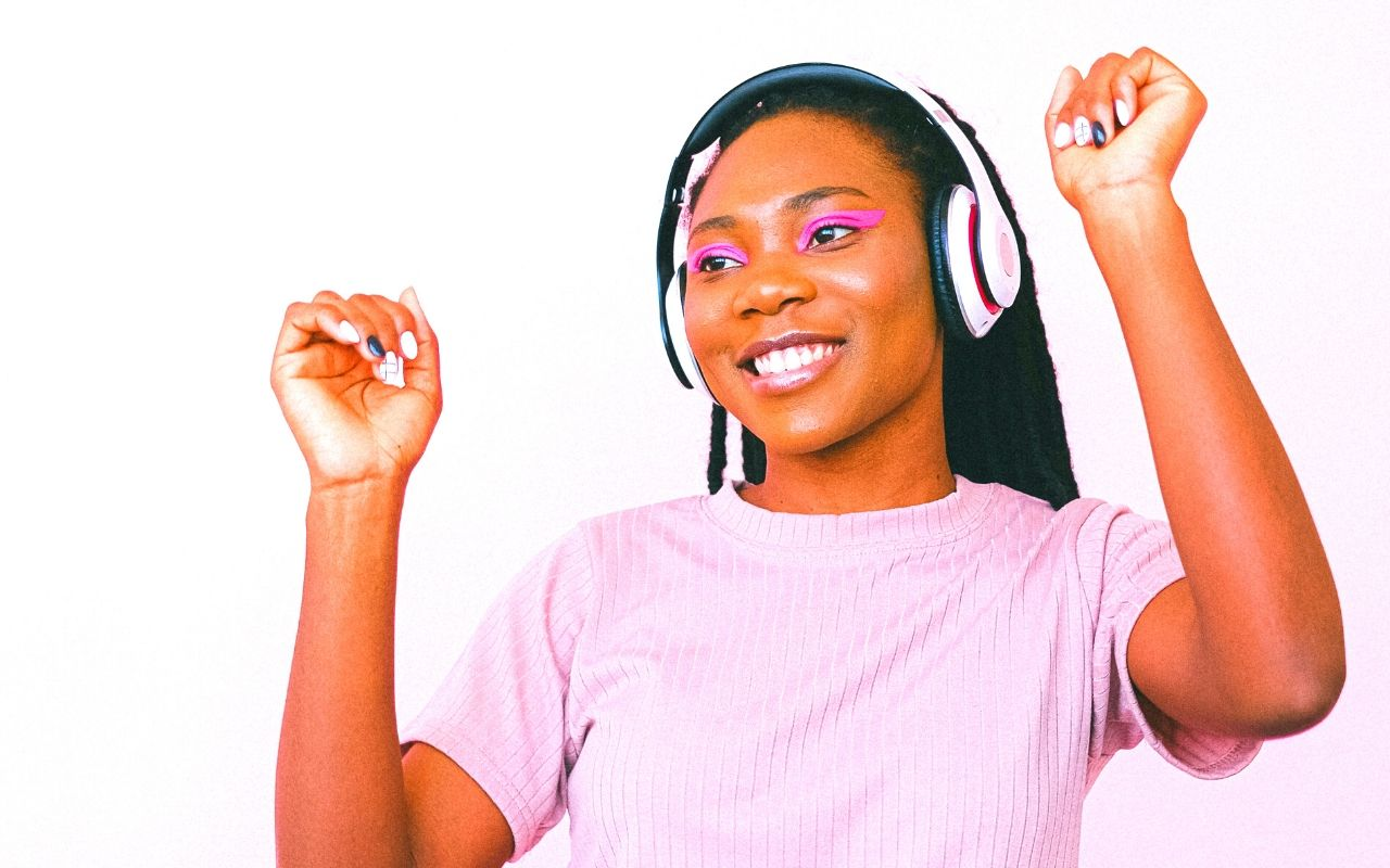 Girl dancing to music with white headphones on