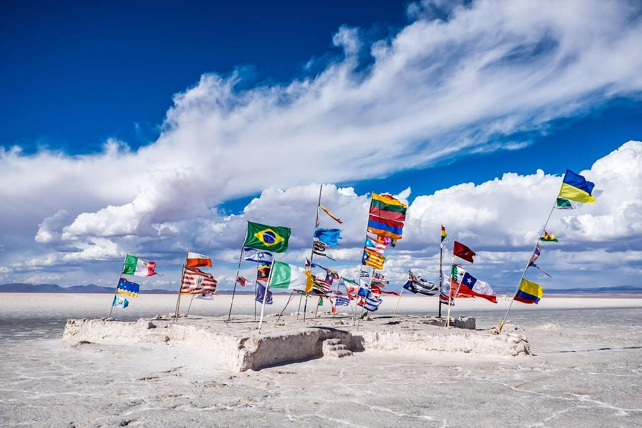 Imagen de una variedad de banderas en una playa de arena