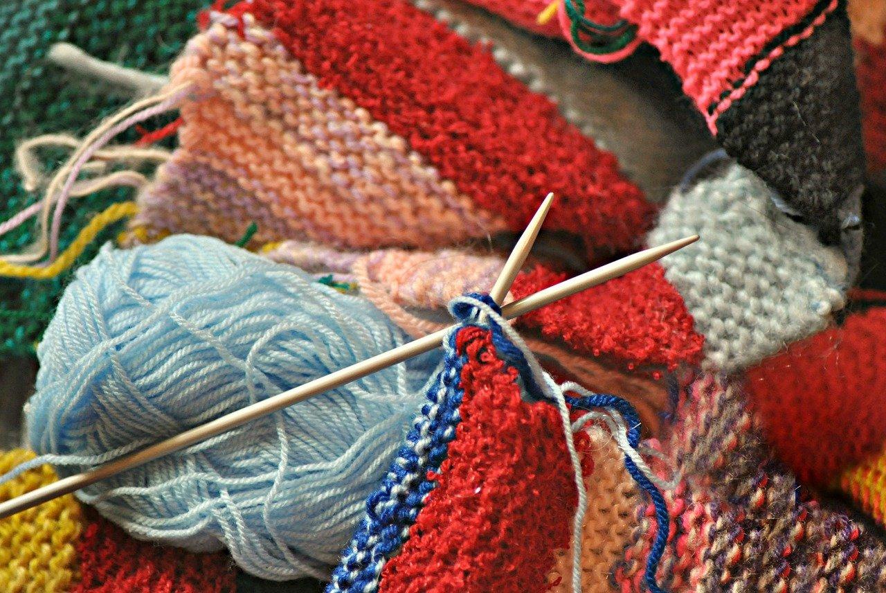 Imagen de patio en varios colores y un par de agujas de tejer