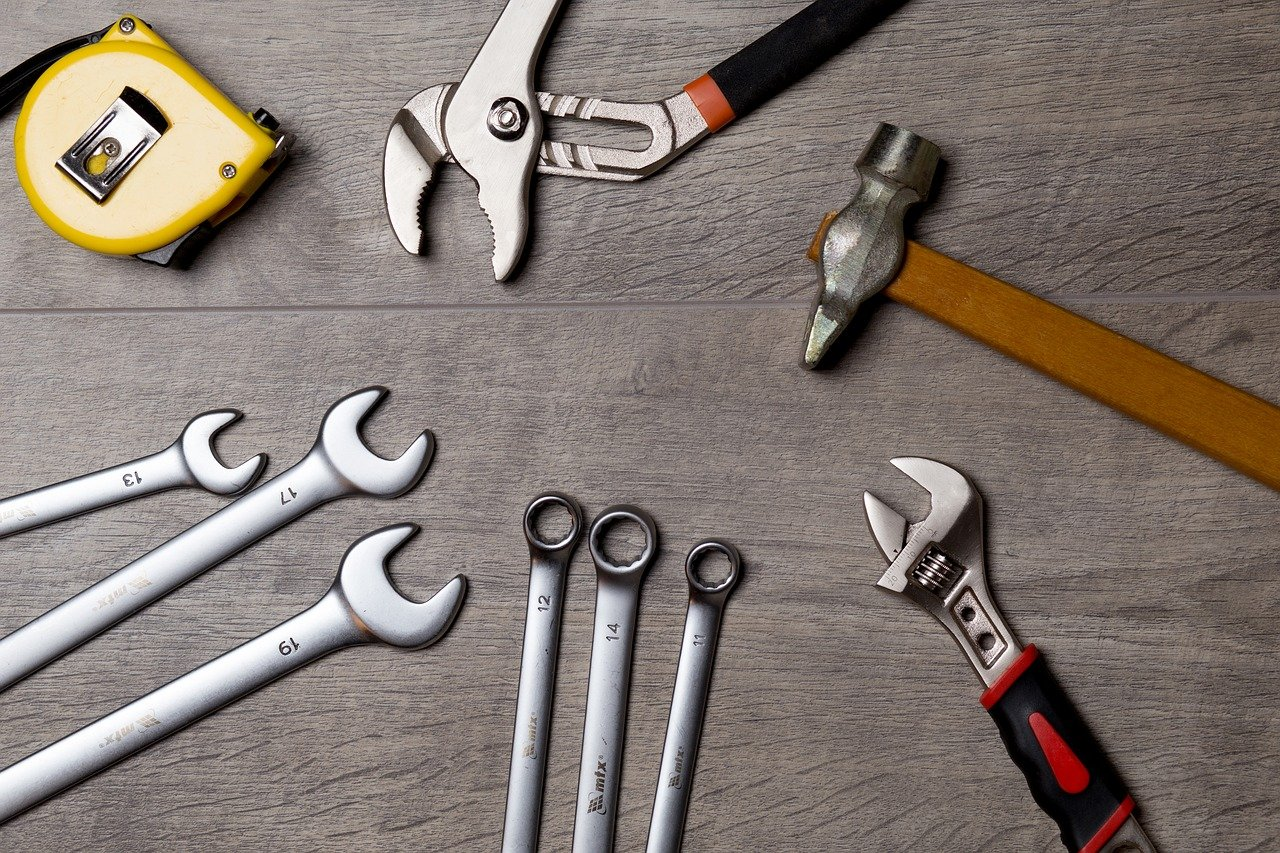 Una imagen de llaves, cinta métrica, martillo y otras herramientas sobre una mesa