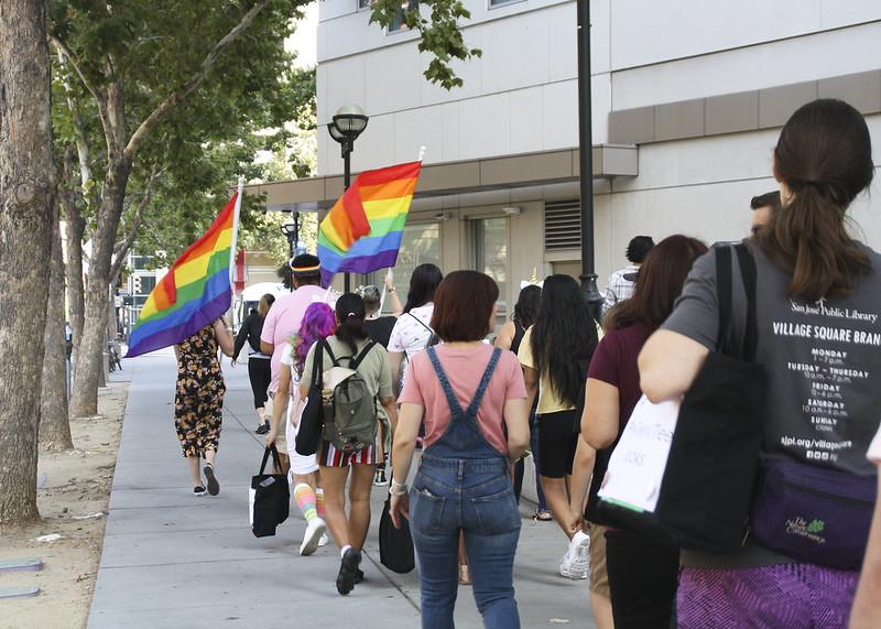 Una fotografía tomada detrás de un grupo de personas que caminan por una calle de la ciudad siguiendo dos banderas del arco iris en la distancia.