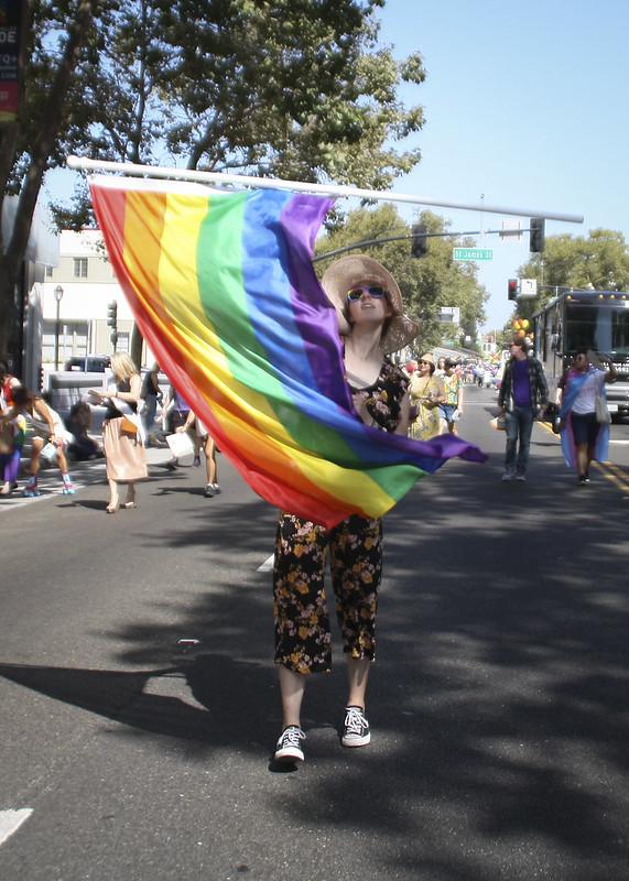Fotografía de una persona joven que camina en un desfile girando alegremente una bandera del arco iris.