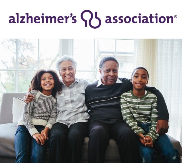 Un retrato informal de una sonriente familia negra de abuelos y nietos sentados en casa. Encima de ellos, en un texto morado, se lee Alzheimer's Association.