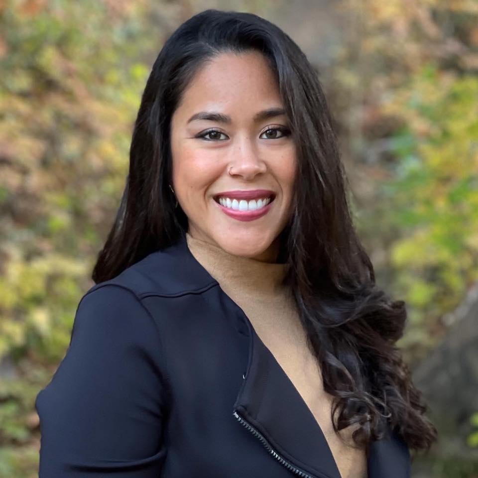 Retrato de la Dra. Angélica Cortez. Ella tiene el pelo largo y negro, lleva una chaqueta azul y una camisa color canela.