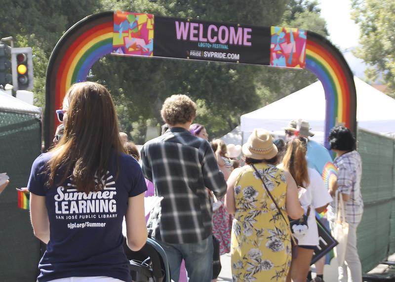 Una foto tomada desde detrás de un grupo diverso de personas entrando en una entrada con arco de arco iris al espacio del Festival LGBTQ del Orgullo de Silicon Valley. En primer plano hay una persona de pelo largo que lleva una camiseta con la San Jose Public LibraryLogotipo de Summer Learning.