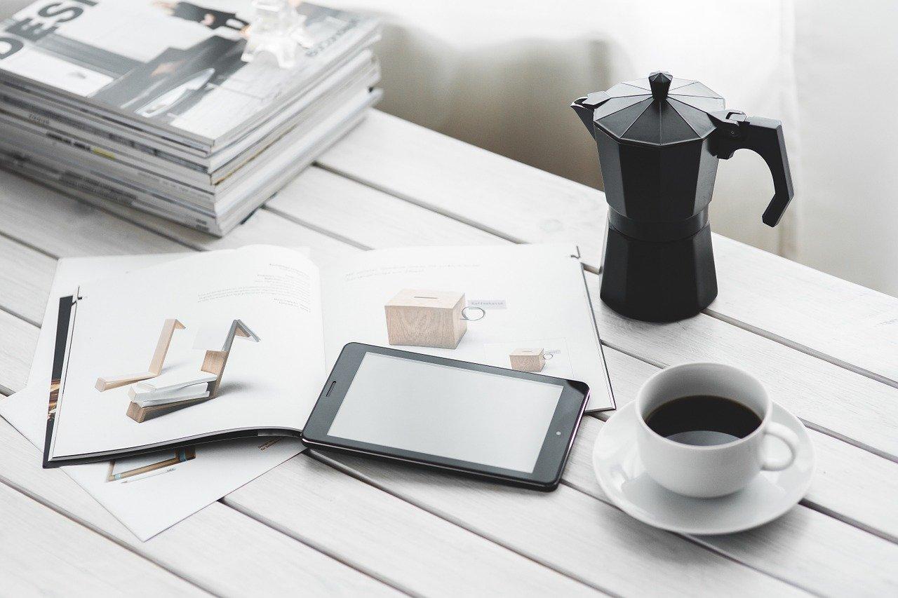 Imagen de una revista, eTablet, cafetera y taza de café sobre una mesa blanca