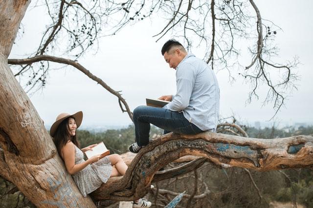 Una foto de un hombre y una mujer sentados en un árbol leyendo entre sí.