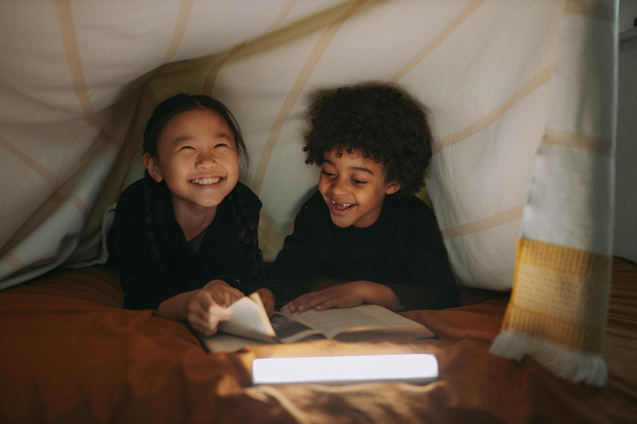 Foto de un niño y una niña sonriendo mientras leen un libro juntos debajo de una manta.