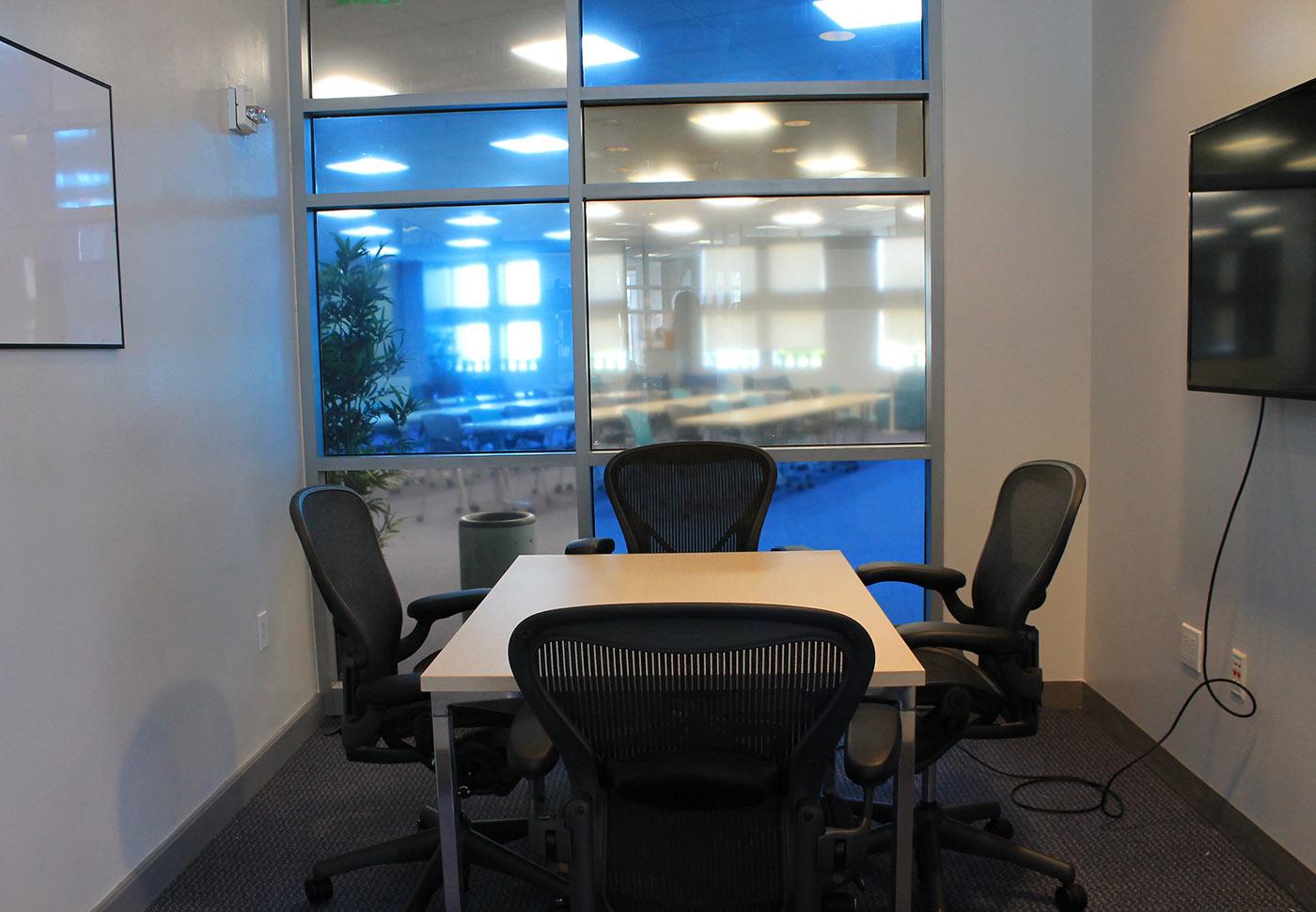 Sala con mesa y cuatro sillas, pizarra y monitor en paredes opuestas.