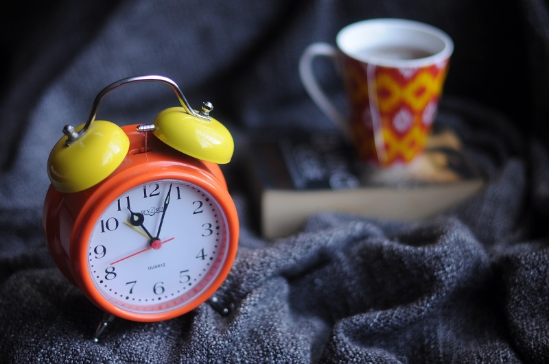 Orange and yellow alarm clock with a book and mug of tea on a navy blanket