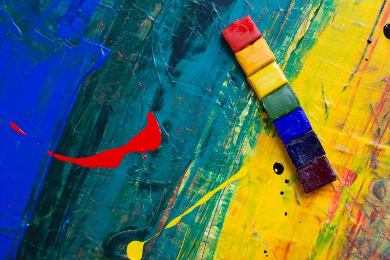 Superficie de madera pintada de colores rojo, naranja, amarillo, verde, azul, índigo y violeta pigmentos de pintura colocados en la parte superior que simboliza el Pride Month Rainbow
