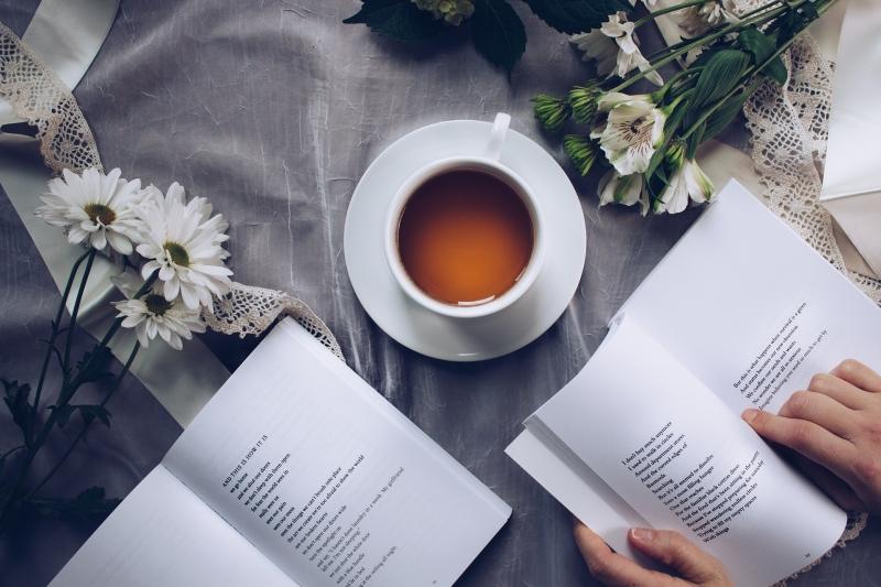 libro de poesía junto a una humeante taza de té