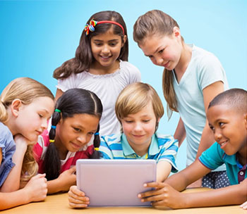 Group of children looking at a laptop.
