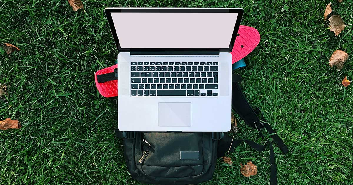 Laptop, atop a skateboard and backpack, on grass lawn.