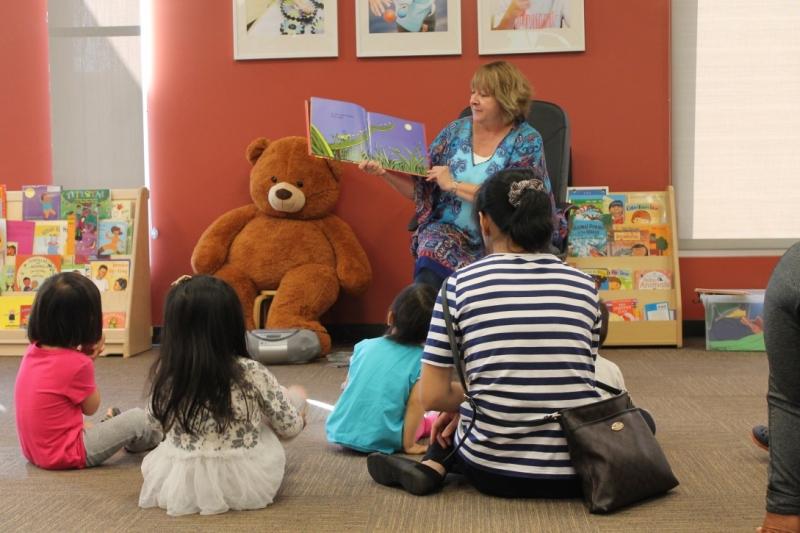 工作人员给坐着的孩子和父母看图画书