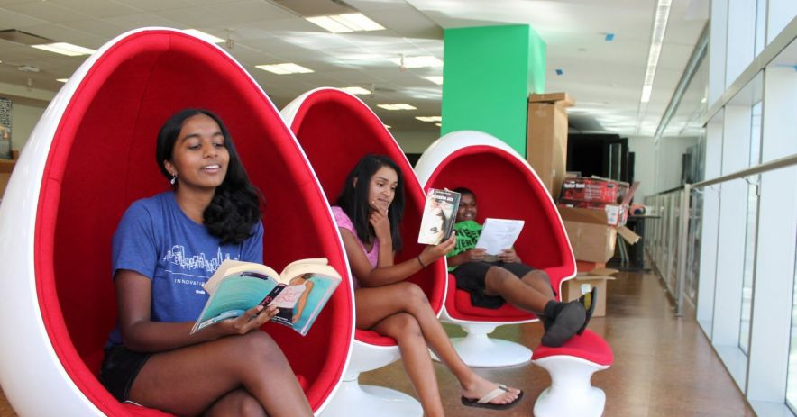 Three teens lounge and read in eggshell chairs