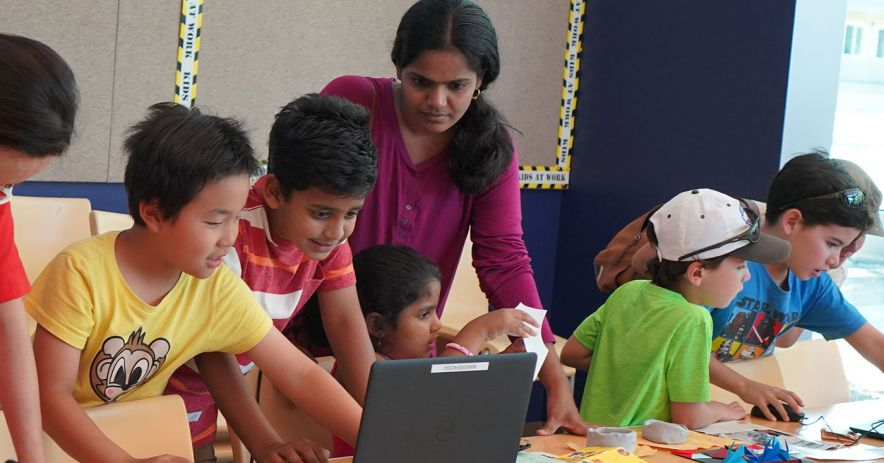 Children excitedly gather around a laptop during a Coding5k class as an adult looks on.