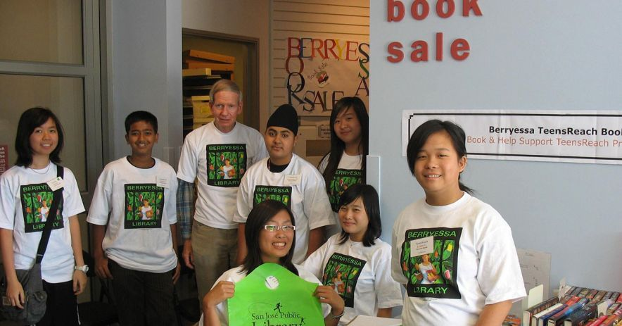 Library Friends wear matching shirts and hold up an SJPL sign at a book sale event