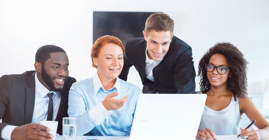 A group of diverse professionals gather around a laptop in a small meeting room.