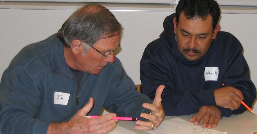A tutor and adult learning study a worksheet together at Partners in Reading.