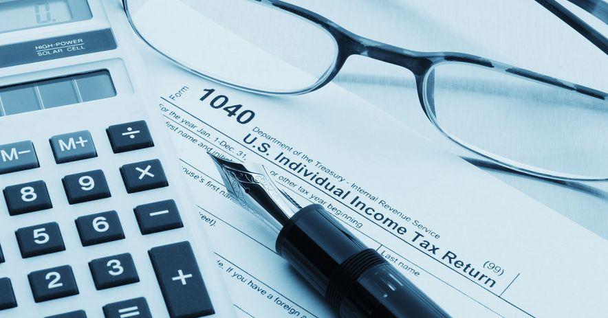 Formulario de impuestos 1040 con calculator, vasos y pluma estilográfica