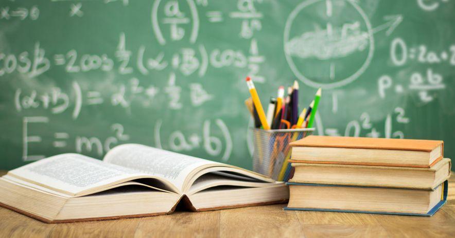 libros y una taza de lápiz se sientan en un escritorio frente a una pizarra cubierta de fórmulas matemáticas.