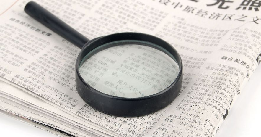 magnifying glass sitting atop a Chinese language newspaper