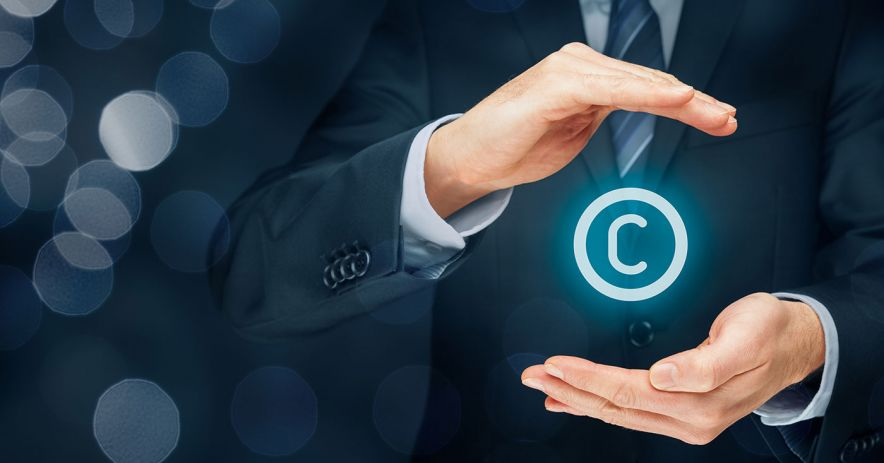 Man in a suit holds a copyright symbol