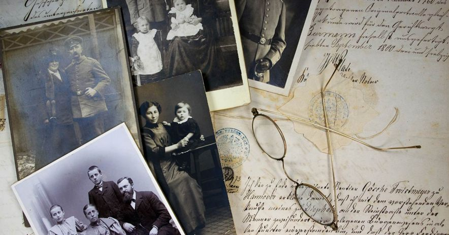 historic family photos and document with antique pair of glasses