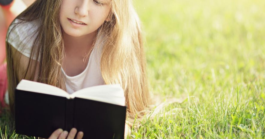 girl reading book in grassy field