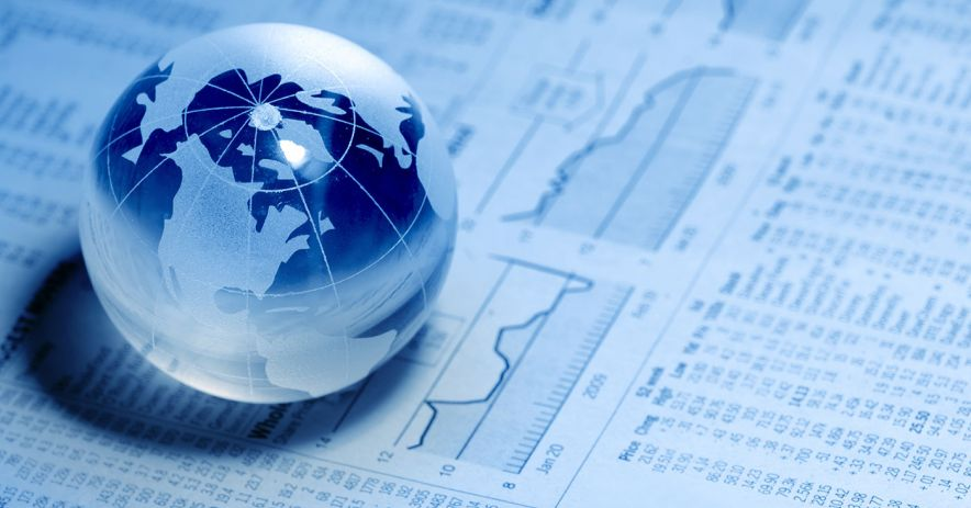 glass globe sitting atop financial charts