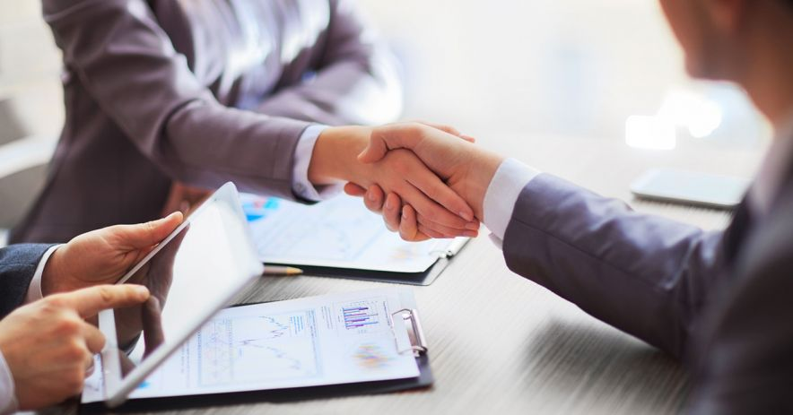 business people shaking hands over a table of charts and papers