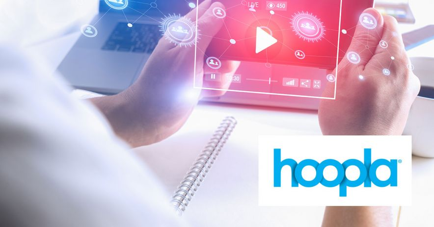 Hoopla logo with image showing person holding device in front of computer.