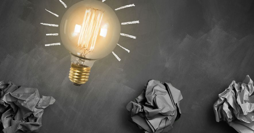 crumpled pieces of paper and glowing lightbulb