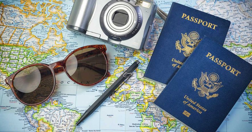 sunglasses, camera, pen, and two U.S. passports lying atop a map of the world