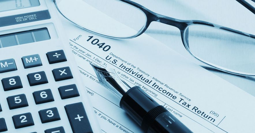 tax form 1040 with calculator, pen, and glasses