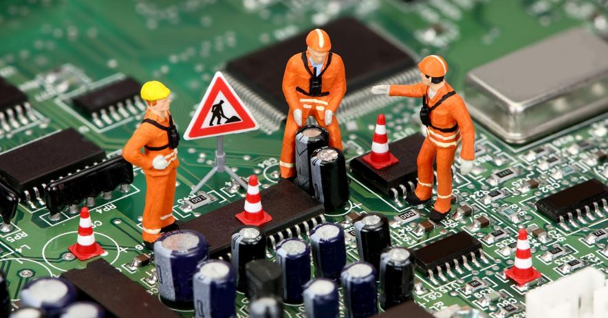 tiny toy construction workers on computer circuit board