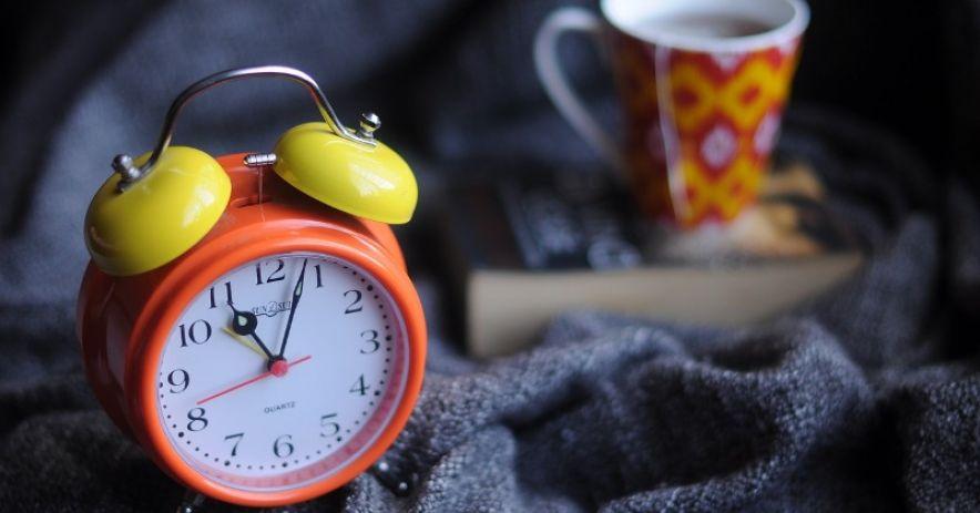Đồng hồ báo thức màu cam và màu vàng với một cuốn sách và cốc trà trên một tấm chăn hải quân