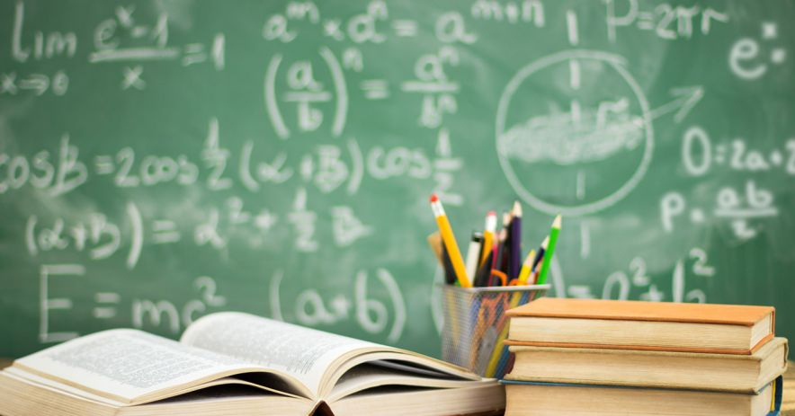 books and a pencil cup sit on a desk in front of a chalkboard covered mathematical formulas.