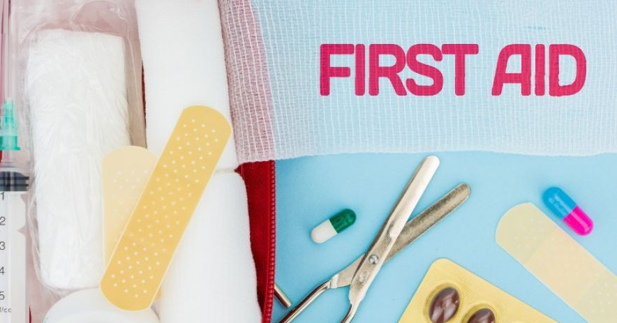 First Aid Kit with bandages, pills, scissors, syringe, and gauze.